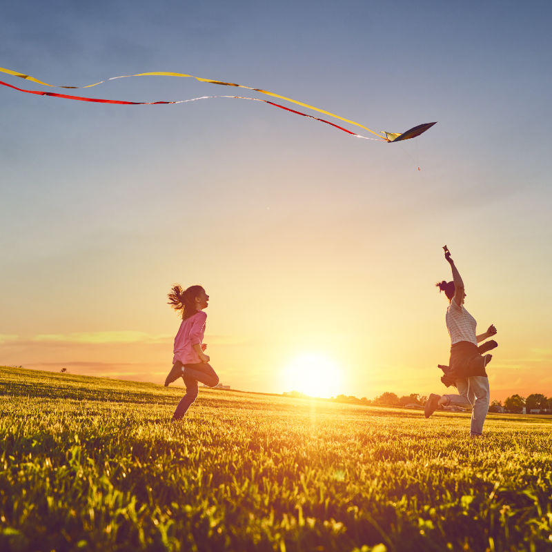 Happy family playing outdoor. Mother and children running on meadow with a kite in the summer on the nature.